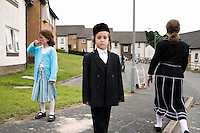 An Hasidic boy called Mr Englander stands outside his family's rented house. Hasidic families stay in Pentre Jane Morgan university accommodation when they holiday in Aberystwyth. Every other day, bread, milk and other supplies are brought from Kosher shops in London and resold from one of the rented houses on the campus.