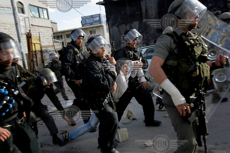 A Palestinian youth is arrested and dragged off by Israeli policemen during riots in the Shuafat Refugee Camp.