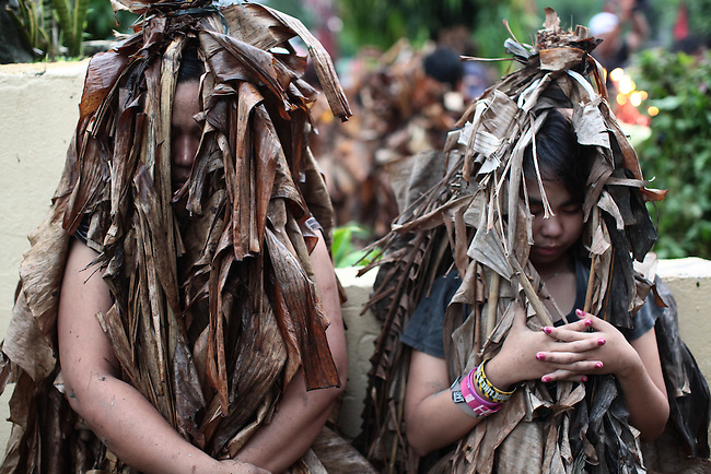 """A mother and daughter pray in front of the Catholic church during the annual Taong Putik, or """"mud people,"""" festival in Bibiclat, on Luzon island, Philippines. The festival honors St. John the Baptist, and devotees cover their bodies with mud, banana leaves and vines to symbolize the animal skins the saint wore in the Bible. June 24, 2011."""