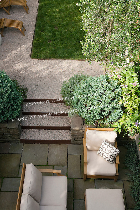 An overhead view of the lower fireplace area and stone steps connecting to the middle lawn area in this multi-level Seattle backyard..