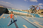 A Young Iraqi boy plays in an abandoned swimming pool built during Saddam's regime. The facility is now used by families who cannot afford rent as a temporary home. ..Stability and security prevail in postwar Iraqi Kurdistan as Iraqi tourists, many of them from Baghdad, flock to the northern cities and their amusement parks and national parks to escape violence and sectarian strife in the central and southern regions of the country.