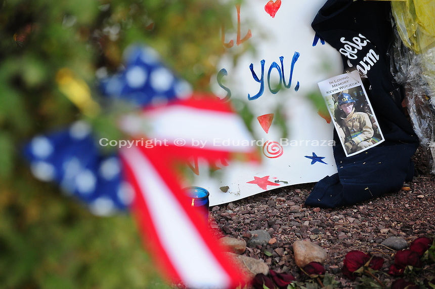 Phoenix, Arizona. July 3, 2013. A small makeshift memorial for the 19 Arizona firefighters who died on June 30 battling the Yarnell Hill wildfire was built outside the Forensic Science Center in Phoenix, where autopsies are being conducted. A sign written by Captain Albert Bandin honors the 19 members of the Granite Mountain Hotshots team who perished fighting a wildfire in the community of Yarnell, Arizona. An American flag in the shape of a ribbon was hanged on a bush outside the building where the coroner's office is conducting autopsies on the 19 firefighters who were part of the Granite Mountain Hotshots team, and died in a the Yarnell Hill fire. Photo by Eduardo Barraza © 2013