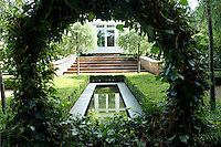 The round ivy-clad plant support leads the eye along the elongated pool to steps leading up to the house in the distance