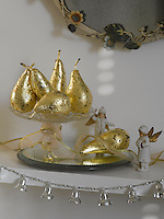 The mantelpiece has been decorated with a string of silver bells and a still life of gilded pears in a glass sweet dish