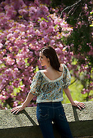 Young woman leans over wall, Flowering Dogwood tree in background