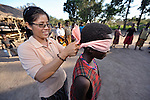 Sister Rosa Le Thi Bong, a Vietnamese member of Sisters of Our Lady of the Missions, ties a blindfold on a girl during a game in the Makpandu refugee camp in Southern Sudan, 44 km north of Yambio, where more that 4,000 people took refuge in late 2008 when the Lord's Resistance Army attacked their communities inside the Democratic Republic of the Congo. Attacks by the LRA inside Southern Sudan and in the neighboring DRC and Central African Republic have displaced tens of thousands of people, and many worry the attacks will increase as the government in Khartoum uses the LRA to destabilize Southern Sudan, where people are scheduled to vote on independence in January 2011. Catholic pastoral workers have accompanied the people of this camp from the beginning. Sister Rosa works in the area as a member of Solidarity with Southern Sudan, a pastoral presence of Catholic priests, sisters and brothers from around the world. NOTE: In July 2011 Southern Sudan became the independent country of South Sudan.