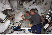 In Earth Orbit - July 6, 2006 -- European Space Agency (ESA) astronaut Thomas Reiter (left) and astronaut Steven W. Lindsey work in the Quest airlock aboard the International Space Station (ISS) during their first day on the orbital outpost. Lindsey, STS-121 commander, will spend a little over a week there, and Reiter is scheduled for a six month stay. Astronaut Piers J. Sellers' extravehicular mobility unit space suit for the scheduled July 8 space walk is in the background..Credit: NASA via CNP