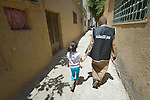 Manal Mustafa walks 5-year old Sarah Rafai through the streets of Madaba, a sprawling Palestinian refugee camp in Jordan that has grown in recent years with the arrival of refugees--like Sara and her family--from war-torn Syria. Mustafa, a volunteer with the Department of Service for Palestinian Refugees of the Middle East Council of Churches, a member of the ACT Alliance, is escorting the girl to a clinic that the organization runs for residents of the camp.