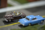Hicksville, New York, USA. February 22, 2015. A blue classic model car and brown model car with driver and passengers are in road scene display at the Model Train Exhibit is hosted by Trainville Hobby Depot at the Broadway Mall. Donations were accepted at exhibit to support the Nassau County Empire State Games for the Physically Challenged.