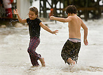 Kaylee Maund, 6, (L) and her brother Devin, 7, from Chiefland, Florida play in the waves created by Tropical Storm Alberto at a Cedar Key, Florida beach June12, 2006. REUTERS/Scott Audette