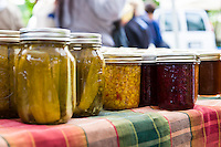 Jars of homemade corn relish and pickled cucumbers by Growing Spaces.