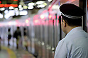 Tokyo, Japan - A train conductor monitors the train platform at Shibuya Station. Morning commuters typically spend over one hour on the train going to work. Trains are usually so packed that train platform staff have to push commuters to fit in the train so that the doors can close shut. (Photo by Yumeto Yamazaki/AFLO)