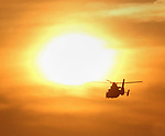The a helicopter flies towards the setting sun as seen from Aquatic Pier, San Francisco, CA.