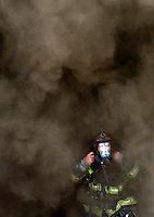 Photo by Gary Cosby Jr.  An unidentified Decatur firefighter straps on his breathing apparatus amid swirling clouds of smoke while helping fight a fire in the Chick-Fil-A restaurant on Beltline Rd. SW in Decatur, Ala., Wednesday, August 1, 2007.  Workers in the restaurant said the fire started in a fryer.  No injuries were reported in the blaze.