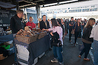 """Customers shop at Nordic Breads bakery at the New Amsterdam Market on South Street in New York during the market's opening day for the season, Sunday, April 29, 2012. The market, located in the former Fulton Fish Market, features vendors who source their artisanal food directly from local farmers and stands of the farmers'  themselves . For opening day they promoted their """"Bread Pavilion"""" which had booths from 16 local artisanal bakeries. (© Richard B. Levine)"""