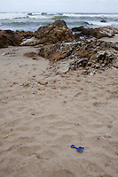 An abandoned toy shovel left behind in the sand, with rocks and surf in the background at Pescadero State Beach, California.