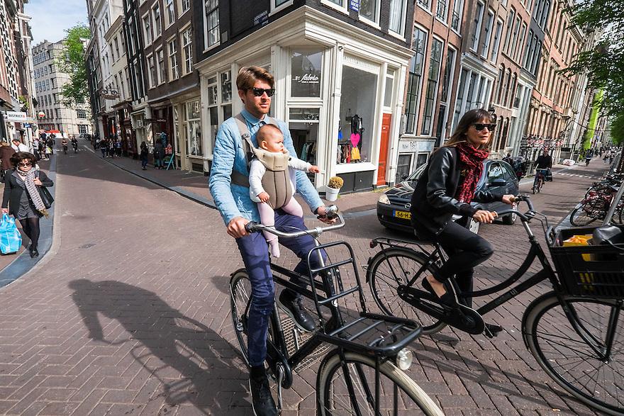Nederland, Amsterdam, 30 mei 2015<br /> Jonge vader fiets met baby in draagzak door de stad.  <br /> Foto: Michiel Wijnbergh