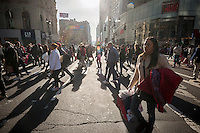 Hordes of shoppers laden with their purchases cross Herald Square in New York on the day after Thanksgiving, Black Friday, November 27, 2015. The National Retail Federation estimates that 135.8 million American will shop in person and online during the four day Thanksgiving weekend.  (© Richard B. Levine)
