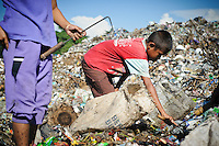 Idris, 13, searching for plastic and metal to recycle amongst newly dumped waste at the 'Trash mountain', Makassar, Sulawesi, Indonesia.
