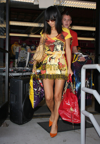 BAI LING.Bai Ling Visits the Ed Hardy Corporate Outlets held at Ed Hardy Outlets, Los Angeles, California, USA..July 4th, 2009.full length dress yellow brown print pattern red shiny patent large oversized bag purse orange shoes sunglasses shades.CAP/ADM/KB.©Kevan Brooks/AdMedia/Capital Pictures.