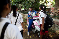 Razia Shabnam (in blue) leaves on her pink scooter after she conducts a boxing training session with a group of girls from an NGO in a park in Basduni, Tolly Gunge, Calcutta, West Bengal, India. Razia Shabnam, 28, was one of the first women boxers in Kolkata. She was also the first woman in her community to go to college. She is now a coach and one of only three international female boxing referees in India.  Photo by Suzanne Lee for Panos London
