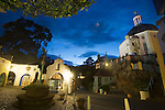 "Portmeirion, in North Wales, is a resort, where no one has ever lived. A self-taught Welsh architect named Sir Clough Williams-Ellis built it out of architectural salvage between the 1920s and 1970s, loosely based on his memories of trips to Portofino. Including a pagoda-shaped Chinoiserie gazebo, some Gothic obelisks, eucalyptus groves, a crenellated castle, a Mediterranean bell tower, a Jacobean town hall, and an Art Deco cylindrical watchtower. He kept improving Portmeirion until his death in 1978, age 94. It faces an estuary where at low tide one can walk across the sands and look out to sea. At high tide, the sea is lapping onto the shores. Every building in the village is either a shop, restaurant, hotel or self-catering accomodation. The village is booked out at high season, with numerous wedding receptions at the weekends. Very popular amongst the English and Welsh holidaymakers. Many who return to the same abode season after season. Hundreds of tourists visit every day, walking around the ornamental gardens, cobblestone paths, and shopping, eating ice-creams, or walking along the woodland and coastal paths, amongst a colourful assortment of hydrangea, rhododendrons, tree ferns and redwoods. The resort boasts two high class hotels, a la carte menus, a swimming pool, a lifesize concrete boat, topiary, pools and wishing wells. The creator describes the resort as ""a home for fallen buildings,"" and its ragged skyline and playful narrow passageways which were meant to provide ""more fun for more people."" It does just that.///Night shot of The Prisoner and Pocket Money Shops and Dome gallery. The Prisoner is a television cult series starring Patrick McGoohan filmed at Portmeirion. The Prisoner shop is his home in the TV series."