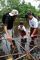Bapak Juanda Datundugon with children during an environmental education class in a mangrove area, Dudepo, Bolmong Selatan, Sulawesi, Indonesia.