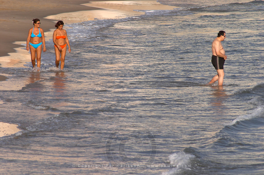 The beach. Two women in bikini. Walking in the water. A man in trunks. Sitges, Catalonia, Spain