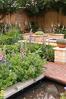 Fireplace firepit fire pit bbq in beautiful patio garden with foxglove Digitalis flowers, geranium, herb thymes Thymus in pot container, water garden, brick walk and stone walls, privacy fence for sense of enclosure creating an outdoor room in the backyard landscaping, with John Keats poem quote on back wall: A thing of beauty is a joy forever. its loveliness increases; it will never pass into nothingness