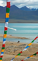 Prayer Flags  and a Horse Rider at Lake Namtso, a Holy Lake for Tibetans at an elevation of 4800 meters and the highest saltwater lake in the world.