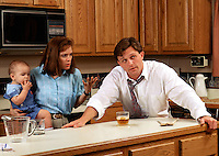 Domestic scene of angry mother holding infant as father avoids communication and hovers over his drink.