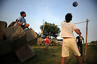 Children playing volleyball beside some left over concrete blocks which were used in a failed attempt to block the mud from surfacing. Since May 2006, more than 10,000 people in the Porong subdistrict of Sidoarjo have been displaced by hot mud flowing from a natural gas well that was being drilled by the oil company Lapindo Brantas. The torrent of mud - up to 125,000 cubic metres per day - continued to flow three years later.
