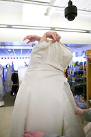 "A bride-to-be tries on a discounted wedding dress with assistance from friends and family during the annual ""Running of the Brides"", a a first-come-first-served bridal gown sale, at the Filene's Basement store in New York City, USA, 3 March 2006."
