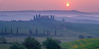 Tuscany, Italy, <br /> Sunrise over a Tuscan farmhouse standing above the misty hills of the Val d'Orcia with the hill town of Pienza on the distant horizon