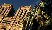 """View from below of equestrian statue of Charlemagne, """"Charlemagne et ses Leudes"""", by the brothers Charles and Louis Rochet, installed in 1882, Place du Parvis-Notre-Dame, Paris France, with the towers of Notre-Dame Cathedral in the background. The bronze horse rears in surprise, its mouth wide open, as if frozen in motion. Picture  by Manuel Cohen."""