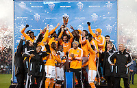 Houston Dynamo captain Brad Davis holds the trophy aloft as the team poses after the game at RFK Stadium in Washington,DC. D.C. United tied the Houston Dynamo, 1-1.  With the tie, Houston won the Eastern Conference and advanced to the MLS Cup.