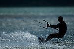 A kiteboarder silhouetted by the evening sun, at the Spit in Squamish, BC, Canada, July 22, 2009. Photo by Gus Curtis.