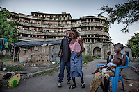 People in front of the former Grand Hotel building. Once a luxury destination for the wealthy and the continent's biggest hotel, the building is now a concrete shell and home to about 6,000 squatters. Those unable to occupy one of the rooms sleep in the corridors, basements and even on the roof of the building.
