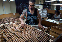 A man smokes a cigar as he selects them to pack at the H. Upmann cigar factory in Havana, Cuba, March 01, 2017. Tourists from around the world visit to Cuba during the annual festival of the cigar, celebrate from February 27 to 3 of March.  VIEWpress/Eliana Aponte.