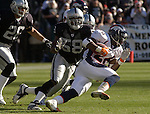 Denver Broncos running back Clinton Portis (26) runs away from Oakland Raiders linebacker Napoleon Harris (58) on Sunday, December 22, 2002, in Oakland, California. The Raiders defeated the Broncos 28-16.