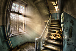 Abandoned lunatic asylum north of Berlin, Germany. Stairwell with sunlight in window.
