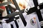 Hooded penitents bearing wooden crosses, Palm Sunday, Seville, Spain