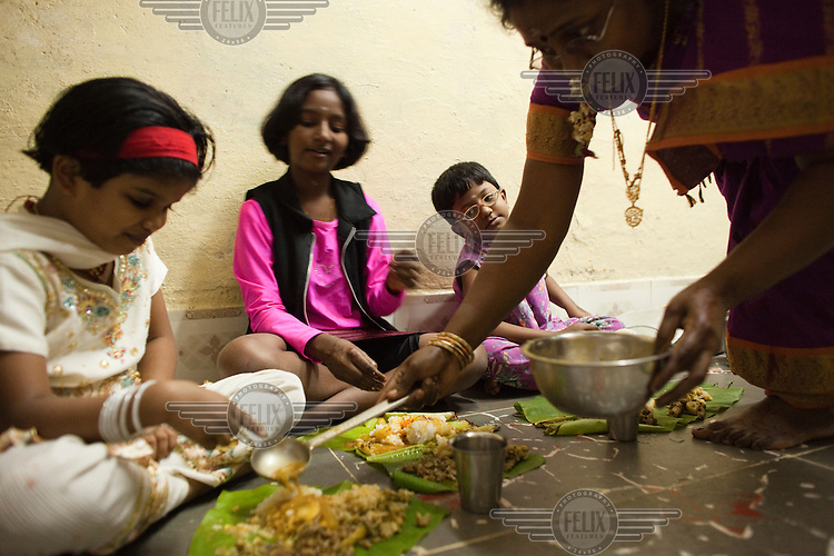 Children eat in their one room family home in Dharavi slum.