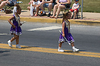 Americana, two young girl baton twirlers march, &..spectators at patriotic hometown parade.