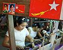 Women weaving silk at a loom. Stickers of NLD red flag with the golden flying peacock were strictly forbidden for two decades until few months ago. They begin to appear in the streets and working places..Mandalay, Myanmar. 2012