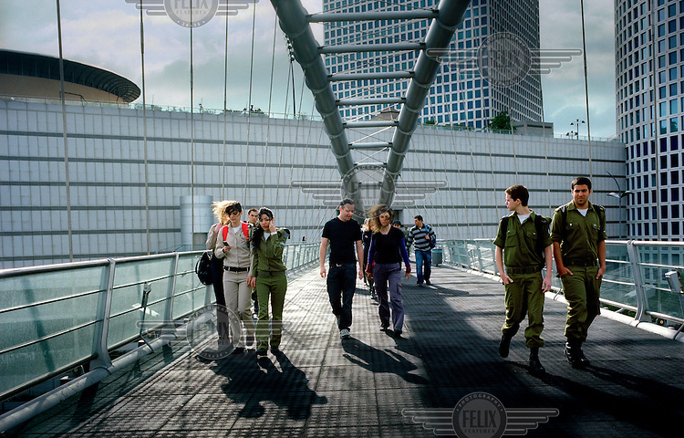 Young Israeli soldiers leave the Azrieli shopping mall in Tel Aviv along with (in the centre), the writer Ron Leshem and NGO activist Miri Weingarten.