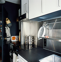 The small, modern kitchen is painted blue and white with a stainless steel splash back