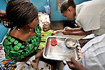 In a clinic of the United Methodist Church in Kananga, a town in the Democratic Republic of the Congo, nurse Agnes Ntumba puts an IV in 7 month old Kabica Kalonda, who is suffering from malaria. His mother, Marie Kalonda, is holding him.