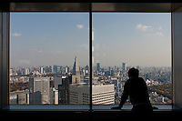 A tourist look out at Shinjuku skyscrapers (including the docomo tower and Roppongi Hills) from the 45th floor observation deck of the Tokyo Metropolitan Government building. Saturday, November 28th 2009