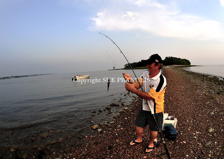 Fisherman catching porgies in shallow water